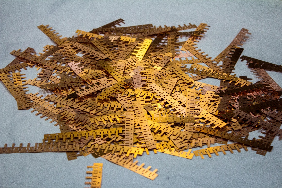 pile of bronze photo-chemically etched parts