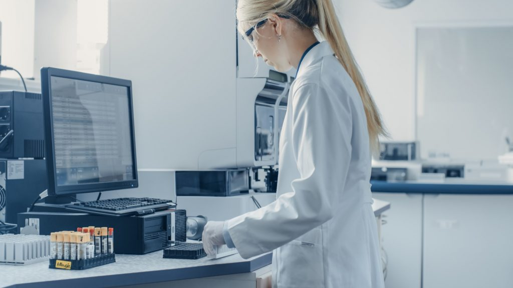 Bio Technological Laboatory Female Research Scientist Analyzes Test Tube in Medical Machine
