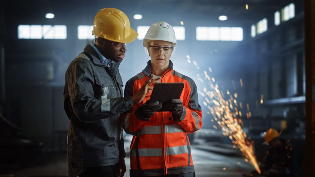 Engineers Stand in Steel Metal Manufacturing Factory, Use Digital Tablet Computer and Have a Discussion