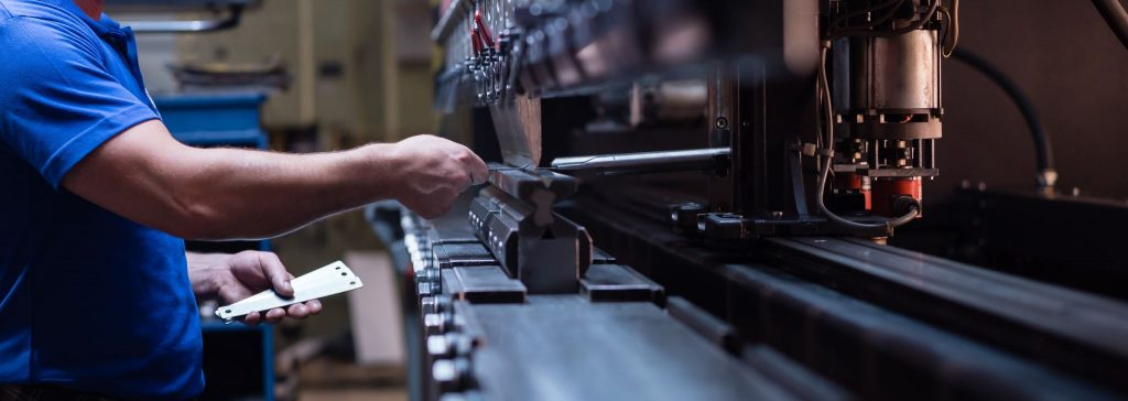 a worker holding a metal plate against a manufacturing machinery